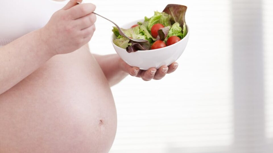 Pregnant woman holding a bowl of fresh salad